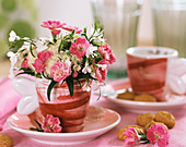 Small arrangement of carnations and lobelia in coffee cup