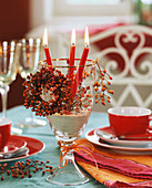 Red candles in a wine glass with small rose hip wreath