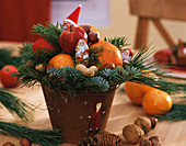 Arrangement with Father Christmases, mandarins, apples & nuts