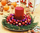 Wreath with red and purple baubles and red candle