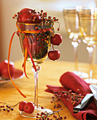 Wine glass filled with red apples, rose hips and moss