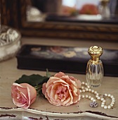 Roses, string of pearls and perfume bottle