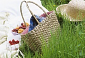 Fruit, basket and straw hat in grass