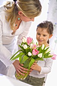 Woman and girl holding vase of tulips