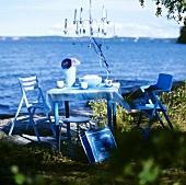 Tisch mit Stühlen und hängendem Kerzenleuchter am See