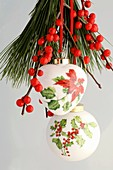 Christmas tree ornaments with holly and poinsettia motifs