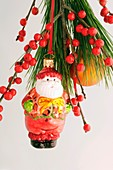 Father Christmas tree ornament & red berries on pine branch