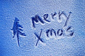 Merry Xmas written on sheet of ice
