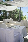 Tables laid in white on the terrace of a restaurant