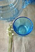 Maiglöckchen neben einem Glas und einer Glaskanne
