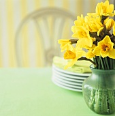Vase of daffodils and pile of plates on a table