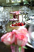 Roses, cherries and chocolate rounds on laid table