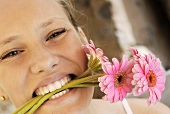 Young woman with pink gerberas in her mouth