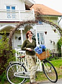 A woman with a bicycle in front of a house