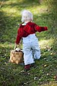 A little girl carrying a basket of mushrooms