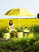 Still life in yellow; woman in front of a rapeseed field in bloom