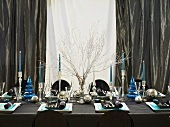 A festively laid Christmas table in blue and silver