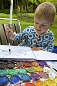 A little girl painting with water colors