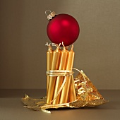 A red Christmas bauble balanced on golden candles