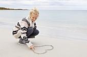 Teenager zeichnet Herz in den Sand am Meer