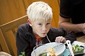 A blond boy eating spaghetti