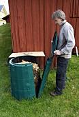 Man opening full compost bin