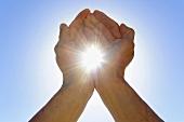 Sun shining between hands held up to sky