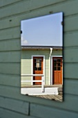 Reflection of a wooden house in a mirror