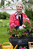 Woman planting up container in garden