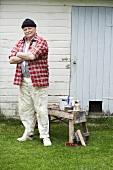 Mann beim Anstreichen einer Holzhütte