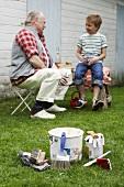 Grandfather and grandchild taking a break in garden
