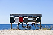 A bike leaning against mailboxes, the ocean in the background
