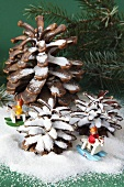 A pine cone and small toy figures on rocking horses