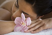 A young woman lying on a massage table with orchid flowers