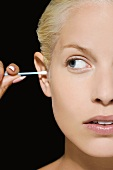 A woman with a cotton bud in her ear