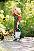 A little girl dressed as a gardener holding a watering can and a sunflower