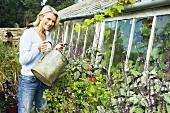 A woman watering plants in a garden