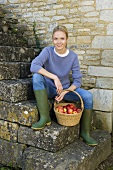 A woman sitting on a flight of stairs with a basket of apples