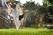 Children jumping through a sprinkler