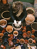 A woman planting flowers in a pot surrounded by lots of empty plant pots