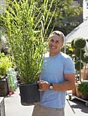 Mann hält eine Topfpflanze im Garten-Center