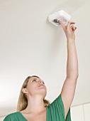 A woman testing a smoke alarm