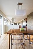 Langgestrecktes offenes Esszimmer mit Tisch, Plexiglas-Stühlen & Deckenleuchte