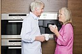 A middle aged couple standing in a kitchen with cups of coffee