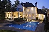 Spiegelnde Wasserfläche eines Pools in der Abenddämmerung mit erleuchtetem Haus im Hintergrund