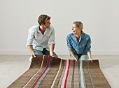 A young couple unrolling a rug