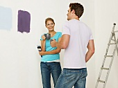 A young couple choosing paint for a wall
