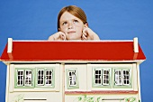 A girl leaning on a dolls' house