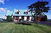 Schönes Haus am See mit türkisfarbenem Dach, Giebelgauben und geteerter Auffahrt