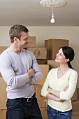 A couple standing in front of cardboard boxes
